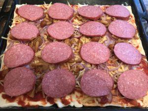 выложите на пиццу порезанную колбасу