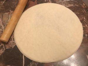 раскатайте тесто для пиццы скалкой или руками
